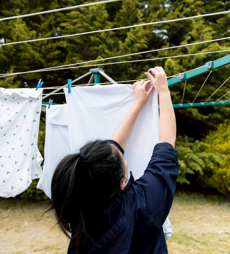 hanging clothes on umbrella clothes dryer